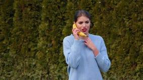La jeune femme attirante de portrait dans la veste bleue met la banane à son oreille et entretiens comme au téléphone banque de vidéos