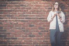 La jeune femme attirante en verres, veste rose de denim se tient dehors sur le fond rouge de mur de briques et utilise le smartph Photos libres de droits