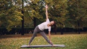 La jeune femme attirante fait le yoga se tenant dehors sur le tapis et l'ordre de pratique de la pose de triangle d'asanas et banque de vidéos
