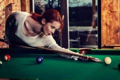 La jeune femme attirante joue le jeu de la table de billard de billard Amusement et concept de concurrence Photos libres de droits
