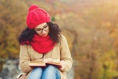 La jeune femme attirante lit le livre en parc et apprécie le jour ensoleillé d'automne Photos libres de droits