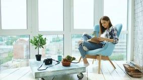 La jeune femme attirante a lu le livre et boit du café se reposant sur le balcon en appartement moderne de grenier Images stock