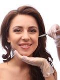La jeune femme attirante obtient les injections cosmétiques, d'isolement au-dessus du fond blanc Mains de médecins Concept de dem image stock