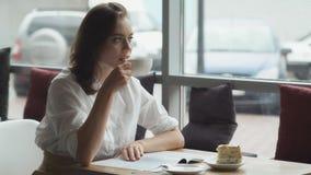 La jeune femme attirante passe le temps gratuit se reposant en cafés, appréciant le café frais et lisant un magazine du ` s de fe photo stock