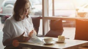 La jeune femme attirante passe le temps gratuit se reposant en cafés, appréciant le café frais et lisant un magazine du ` s de fe photo libre de droits