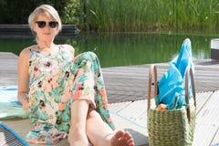 La jeune femme attirante s'assied à la piscine image libre de droits