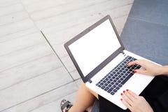 La jeune femme attirante travaille sur l'ordinateur portable image stock