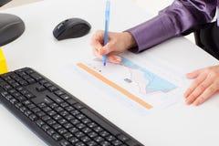 La jeune femme au bureau fait un diagramme financier Image stock