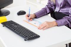 La jeune femme au bureau fait un diagramme financier Photo stock