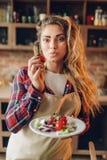 La jeune femme au foyer de sourire dans le tablier pr?pare la salade photos libres de droits