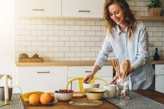 La jeune femme au foyer de sourire se tenant dans la cuisine près de la table fait cuire le dîner, nettoyant des plats La fille f image stock