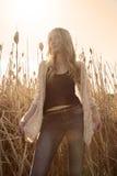 La jeune femme aux cheveux longs se tenant dans extérieur chauffent coloré éclairé à contre-jour Images stock