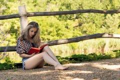 La jeune femme aux pieds nus attirante avec de longs cheveux bouclés est readin Image stock