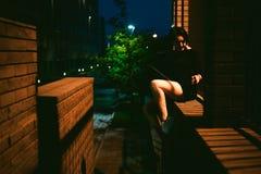 La jeune femme avec de beaux pieds s'est habillée dans les espadrilles et la robe blanches de noir, contre un contexte des paysag Photos stock