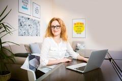 La jeune femme avec de longs cheveux rouges dans la chemise blanche et verres pour la vision travaille, regarde l'appareil-photo, Images stock