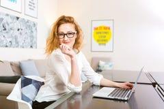 La jeune femme avec de longs cheveux rouges dans la chemise blanche et verres pour la vision travaille, regarde l'appareil-photo, Images libres de droits