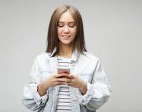 La jeune femme avec de longs cheveux, tient le t?l?phone portable moderne image libre de droits