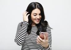La jeune femme avec de longs cheveux, tient le t?l?phone portable moderne photos stock