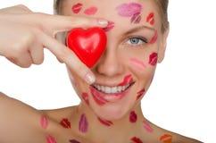 La jeune femme avec des baisers sur le visage tenant le coeur observe Photographie stock