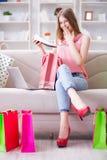 La jeune femme avec des paniers à l'intérieur autoguident sur le sofa Photos libres de droits