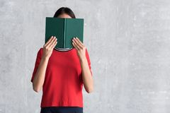 La jeune femme avec du charme couvre derrière livre de contes Photo libre de droits