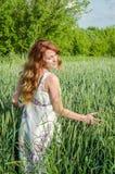 La jeune femme avec du charme marchant dehors dans un domaine près des buissons de vert et des arbres, oreilles de tapotement de  Photo libre de droits