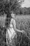 La jeune femme avec du charme marchant dehors dans un domaine près des buissons de vert et des arbres, oreilles de tapotement de  Photos stock