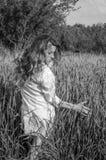 La jeune femme avec du charme marchant dehors dans un domaine près des buissons de vert et des arbres, oreilles de tapotement de  Image libre de droits