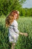 La jeune femme avec du charme marchant dehors dans un domaine près des buissons de vert et des arbres, oreilles de tapotement de  Photos libres de droits