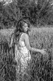 La jeune femme avec du charme marchant dehors dans un domaine près des buissons de vert et des arbres, oreilles ptsenitsy de tapo Photos stock