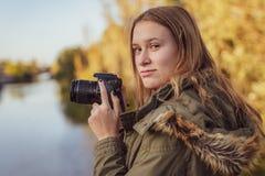 La jeune femme avec l'appareil-photo dans sa main regarde dans l'appareil-photo photos libres de droits