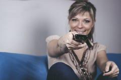 La jeune femme avec la séance à télécommande sur le plan rapproché de sofa s'est concentrée sur à télécommande Image stock