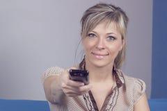 La jeune femme avec la séance à télécommande sur le plan rapproché de sofa s'est concentrée sur à télécommande Photos stock