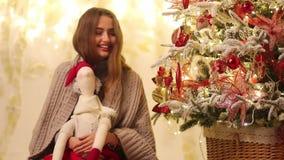 La jeune femme avec le plaid s'assied à côté de l'arbre, des sourires et des jeux de Noël avec Santa Claus dans des ses mains clips vidéos