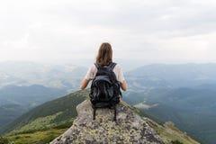 La jeune femme avec le sac à dos de touristes prend le dessus de repos de la colline en montagnes carpathiennes et apprécie le be Photographie stock