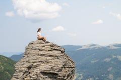 La jeune femme avec le vent dans ses cheveux s'assied sur une roche dans la zone rurale de montagne le jour ensoleillé d'été et a Photographie stock