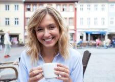 La jeune femme avec les cheveux blonds aime le café Photographie stock