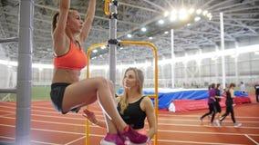 La jeune femme avec les cheveux blonds tire vers le haut sur la barre transversale dans la salle de gymnastique sous la direction banque de vidéos