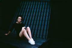 La jeune femme avec les pieds nus s'est habillée dans des espadrilles blanches Photos stock
