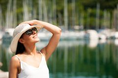 La jeune femme avec la robe et les lunettes de soleil d'été de chapeau marche pilier de m Photo stock