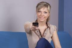 La jeune femme avec la séance à télécommande sur le plan rapproché de sofa s'est concentrée sur à télécommande Photographie stock libre de droits