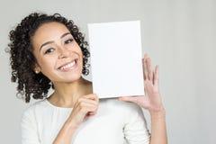 La jeune femme avec un beau sourire tient un conseil vide photographie stock libre de droits