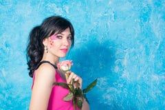La jeune femme avec une rose sourit sur un fond en pastel Photos stock