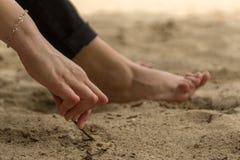 La jeune femme ayant le rhumatisme articulaire prend un repos se reposant sur le sable près de la plage Des mains et les jambes s images stock