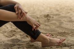 La jeune femme ayant le rhumatisme articulaire prend un repos se reposant sur le sable près de la plage Des mains et les jambes s image stock