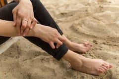 La jeune femme ayant le rhumatisme articulaire prend un repos se reposant sur le sable près de la plage Des mains et les jambes s images libres de droits