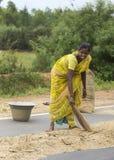 La jeune femme balaye le millet sur la route publique Images stock