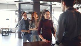 La jeune femme bavarde cause avec le caissier au compteur en café tandis que les personnes impatientes se tiennent dans la ligne  clips vidéos