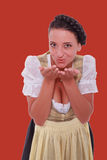 La jeune femme bavaroise dans le dirndl a respiré sur des paumes de vos mains image stock