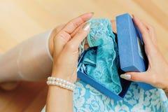 La jeune femme blanche déballe le cadeau avec l'article de lingerie Photos stock